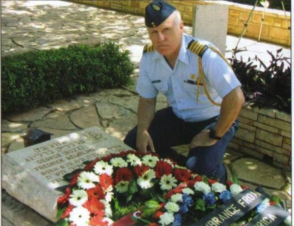 Col Pat Dennis, then Canadian Defence Attaché in Israel, kneels at the grave of F/O Beurling in the Haifa Military Cemetery in Israel.